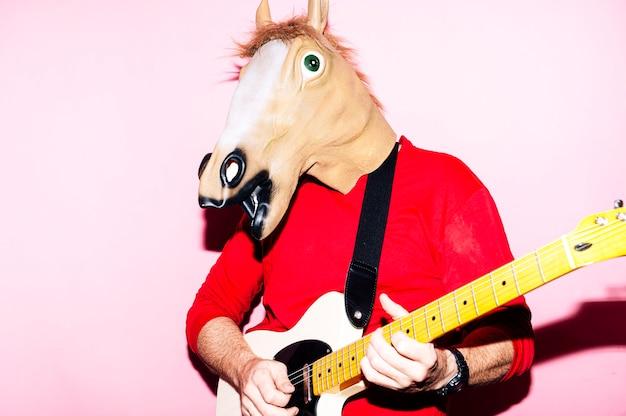 エレクトリックギターを弾く馬のマスクを持つ男 Premium写真