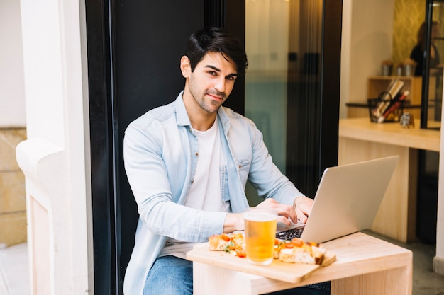 Man with laptop computer relaxing in cafe Free Photo