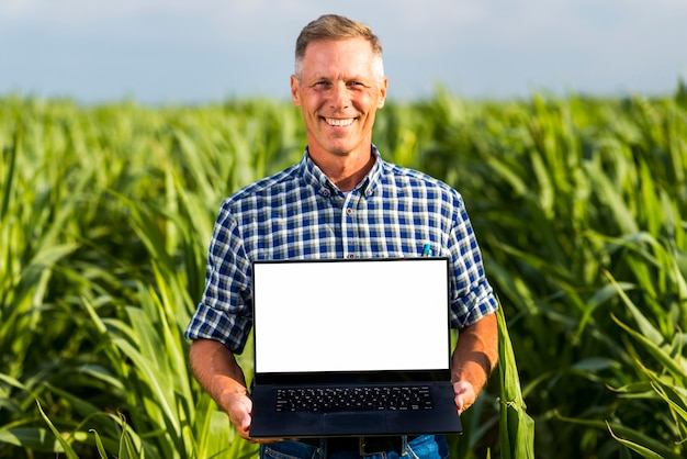 Man with a laptop in a cornfield mock-up Free Photo