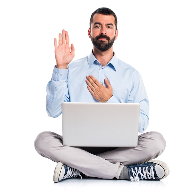 Man with laptop doing an oath Free Photo