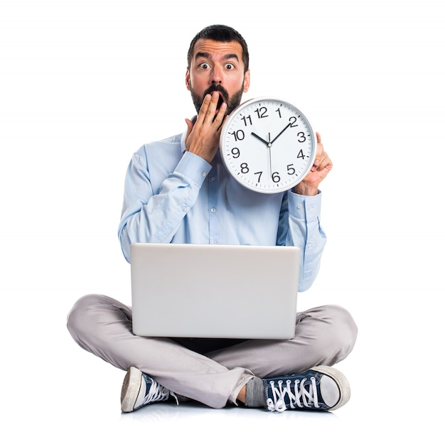 Man with laptop holding a watch Free Photo