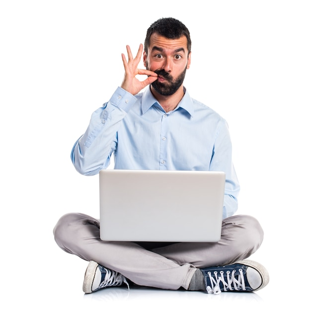 Man with laptop making silence gesture Free Photo