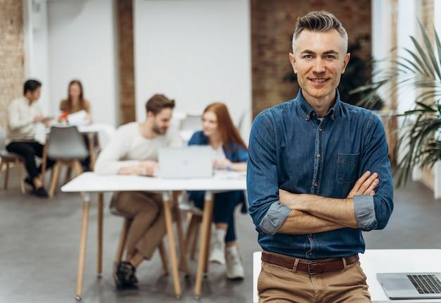 Человек с ноутбуком позирует рядом с коллегами Premium Фотографии