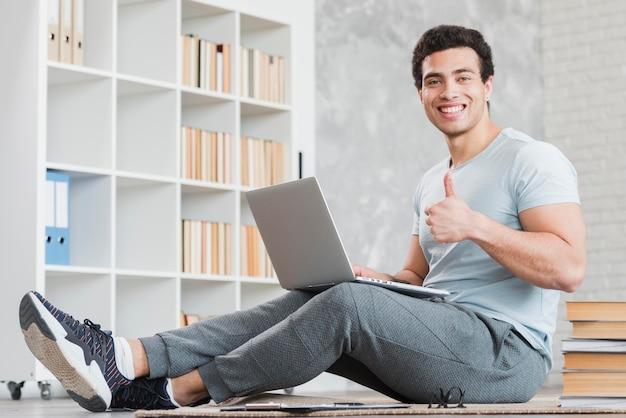 Человек с ноутбуком в окружении книг Бесплатные Фотографии