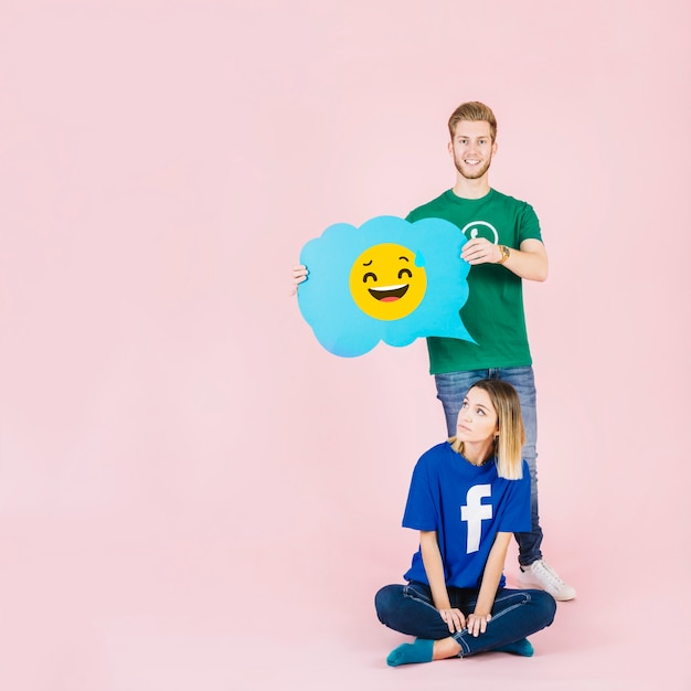 Man with laughing emoji speech bubble standing behind thoughtful woman Free Photo