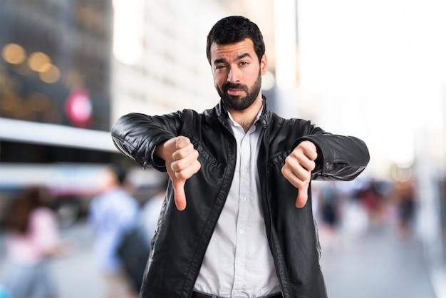 Man with leather jacket doing bad signal Free Photo