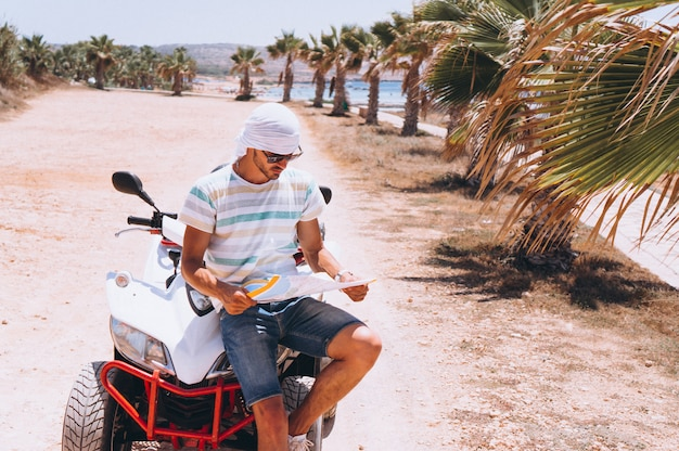 Man with map travalling on atv by the sea Free Photo