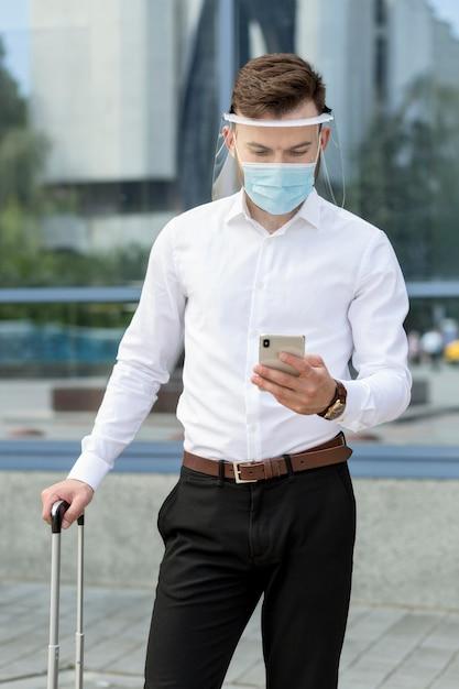 Uomo con la maschera che controlla mobile Foto Gratuite