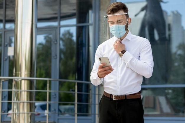 Uomo con maschera utilizzando il cellulare Foto Gratuite