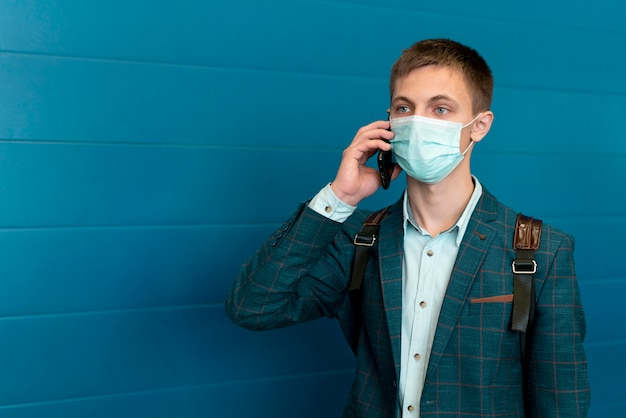 電話で話している医療マスクとバックパックを持つ男 Premium写真