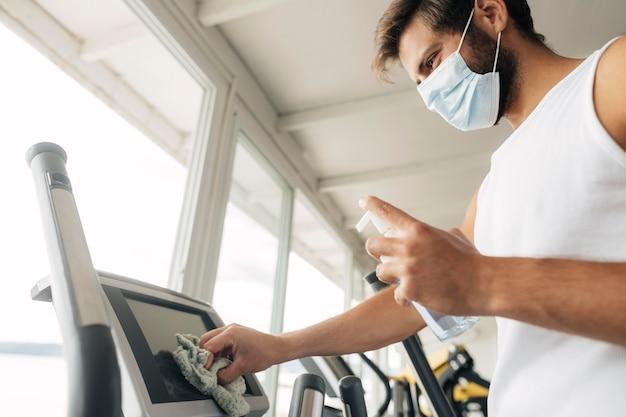 ジム設備を消毒する医療マスクを持つ男 無料写真