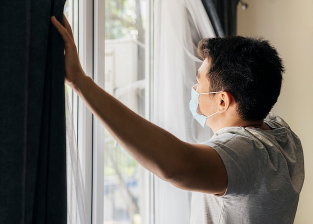 Man with medical mask at home during the pandemic opening the window curtains Free Photo