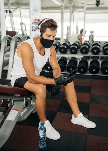スマートフォンを使用しながらヘッドフォンで音楽を聴いている医療マスクを持つ男 Premium写真