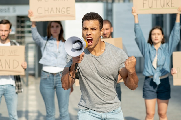 Man with megaphone protesting with activist behind Free Photo