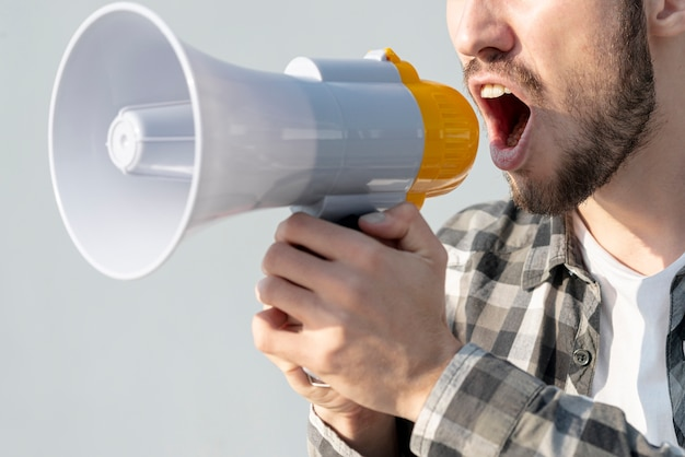 Man with megaphone shouting Free Photo