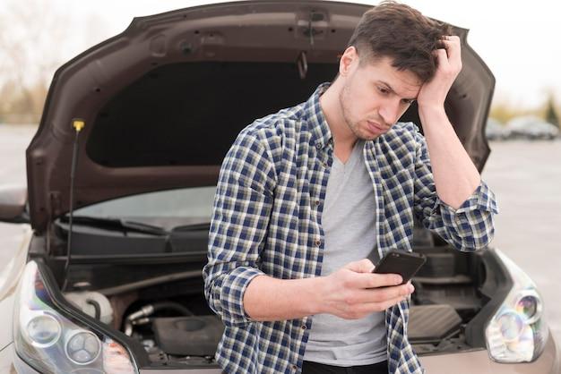Человек с мобильным рядом с разбитой машиной Бесплатные Фотографии
