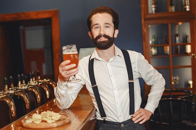 L'uomo con i baffi e la barba sta al bar e beve alcolici da un bicchiere. Foto Gratuite
