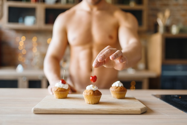 Мужчина с обнаженным телом готовит торты с вишней на кухне. обнаженный мужчина готовит завтрак дома, готовит пищу без одежды Premium Фотографии