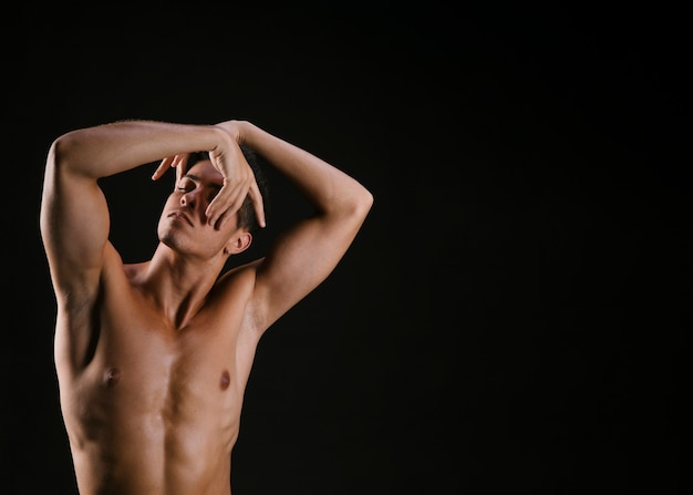 Man with naked torso folding hand before face Free Photo