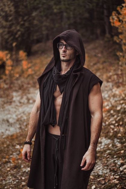A man with a naked torso stands on the  of the autumn forest Premium Photo