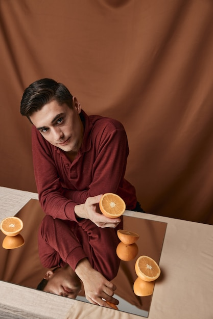 Man with orange oranges on a fabric background and model reflection in the mirror Premium Photo