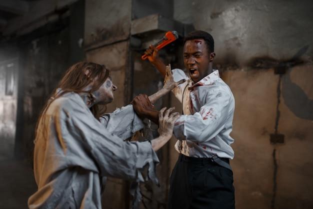 パイプレンチを持った男が女性ゾンビを殺し、致命的な追跡を行う。街の恐怖、不気味な這いつくばりの攻撃、終末の黙示録、不気味な血まみれの怪物 Premium写真