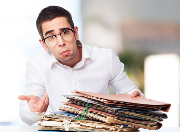 Man with pitying face with a mountain of folders Free Photo