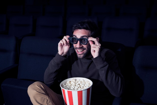 Man with popcorn in cinema Free Photo