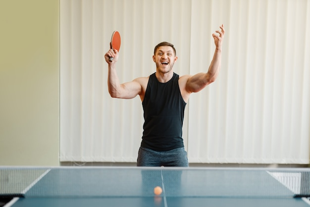 Man with racket in hand wins ping pong tournament indoors. Premium Photo