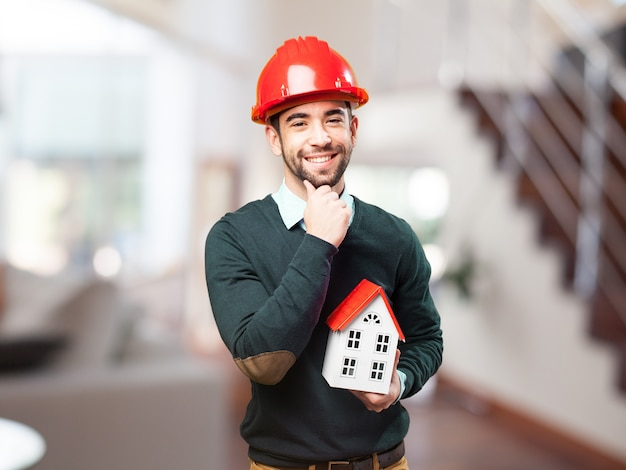 Man with red helmet and a small house in hand Free Photo