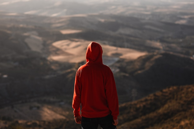 Man with red sweatshirt with blurred landscape Premium Photo