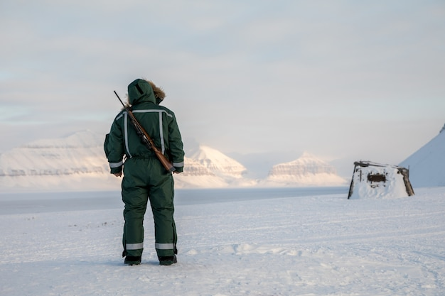 Man with a rifle looks out on the horizon in arctic landscape at svalbard Premium Photo