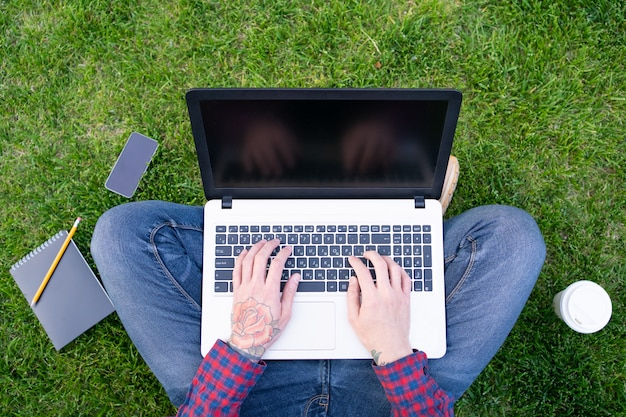 Man with rose tattoo on hand typing on laptop Free Photo