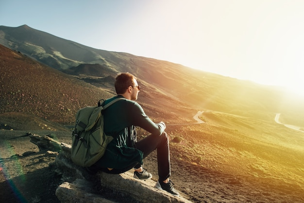 Man with rucksack sitting on rock at sunset on volcano etna mountain in sicily Free Photo