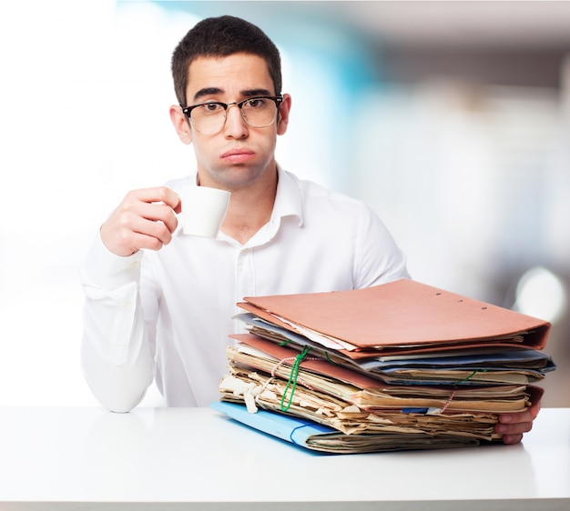 Man with sad face with folders and a cup of coffee Free Photo
