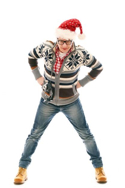サンタ帽子のポーズを持つ男。クリスマスシーズン 無料写真