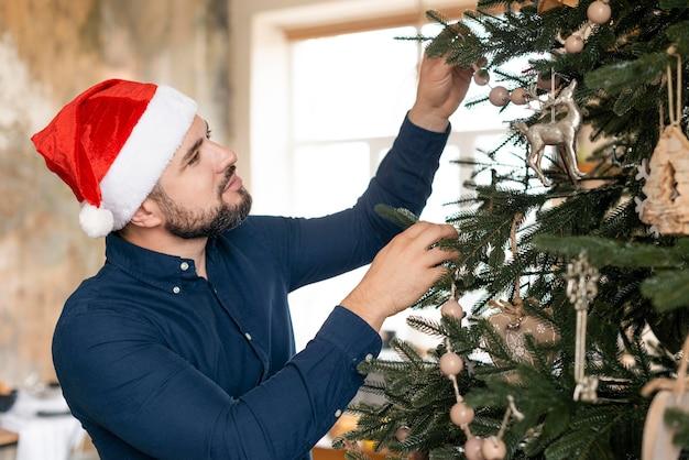 Человек в шляпе санта-клауса украшает дерево Бесплатные Фотографии