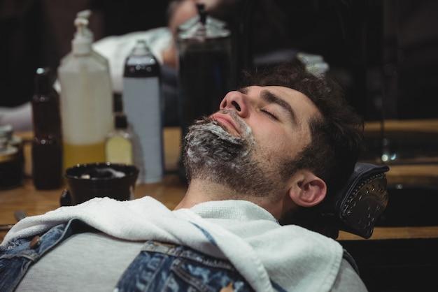 椅子でリラックスしたひげのシェービングクリームを持つ男 無料写真