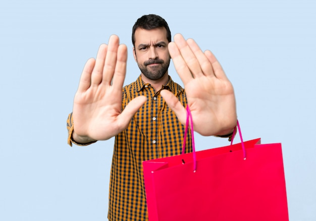 Man with shopping bags making stop gesture for disappointed with an opinion Premium Photo