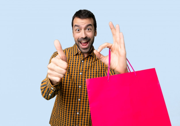 Man with shopping bags showing ok sign with and giving a thumb up gesture on isolated blue background Premium Photo
