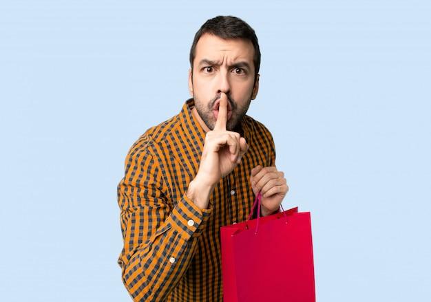 Man with shopping bags showing a sign of silence gesture putting finger in mouth on isolated blue background Premium Photo