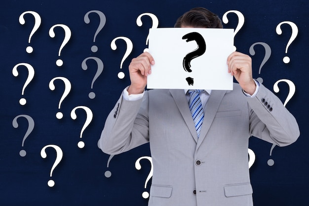 Man with sign with a question mark and a background with question marks Free Photo
