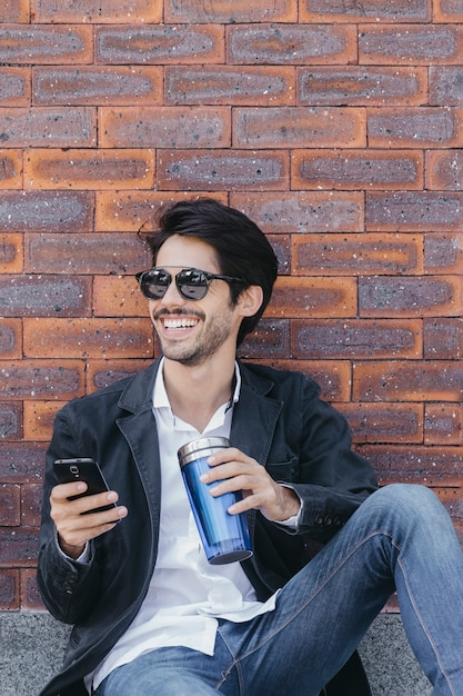Man with smartphone and cup near wall Free Photo
