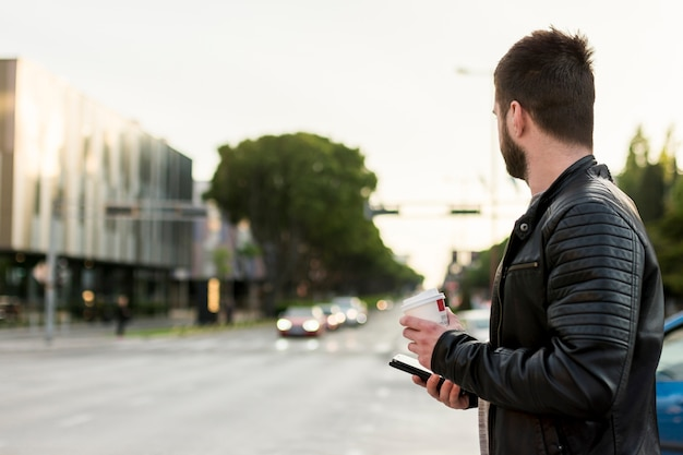 Man with smartphone and coffee crossing street Free Photo