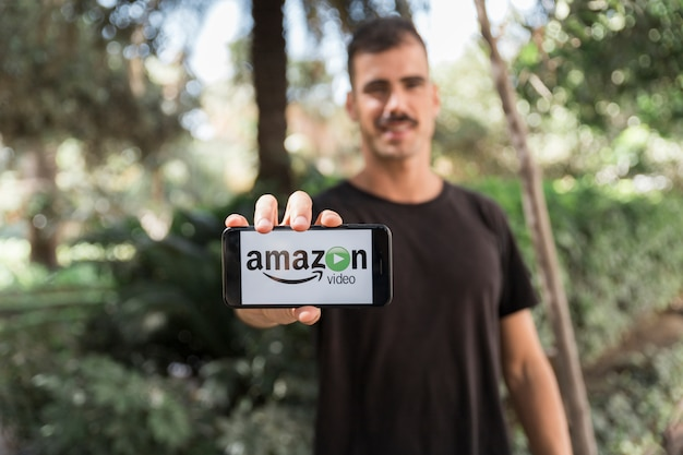 Man with smartphone showing amazon prime video app Free Photo