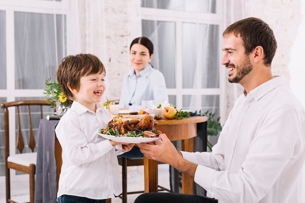 Man with son holding chicken on plate Free Photo