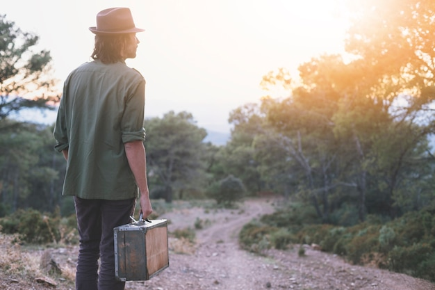 Man with suitcase in countryside Free Photo