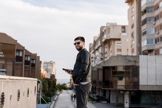 Man with sunglasses holding smartphone Free Photo