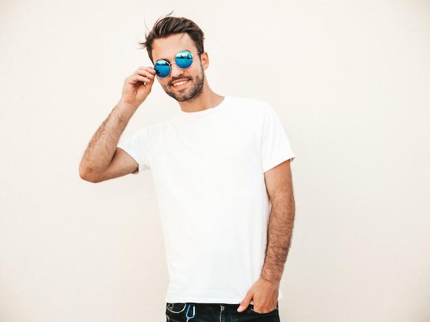 Uomo con gli occhiali da sole che indossano posa bianca della maglietta Foto Gratuite