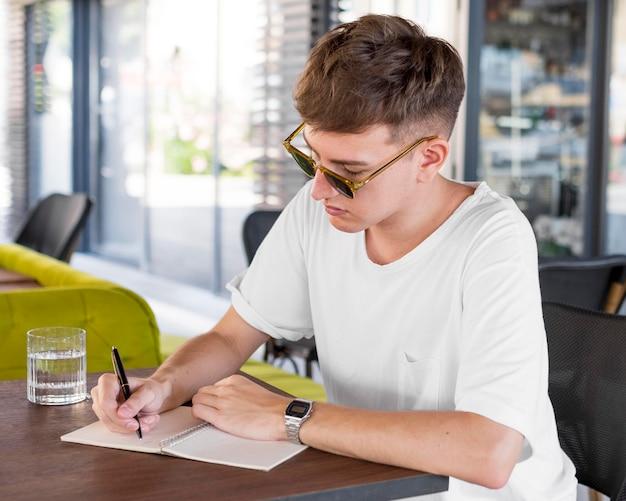 Uomo con occhiali da sole scrivendo al pub Foto Gratuite